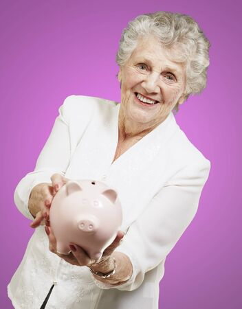 portrait of senior woman showing a piggy bank over pink background photo