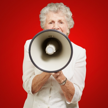 portrait of senior woman screaming with megaphone over red background photo