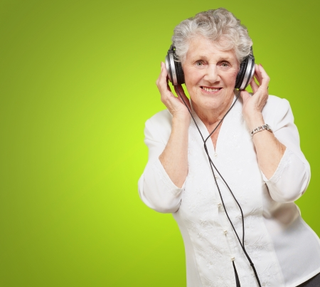 Portrait Of A Woman, While Listening Music On Green Background photo