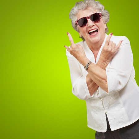 Senior Frau trägt eine Sonnenbrille zu tun flippige Aktion auf grünem Hintergrund