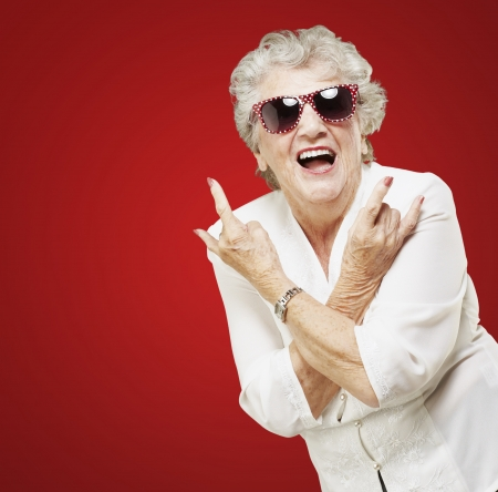 portrait of senior woman doing rock symbol over red background photo