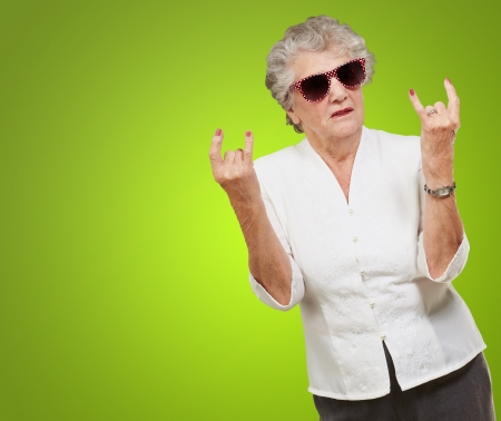 naughty woman: Senior woman wearing sunglasses doing funky action isolated on green background
