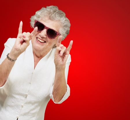 portrait of a happy senior woman doing rock symbol over red background photo