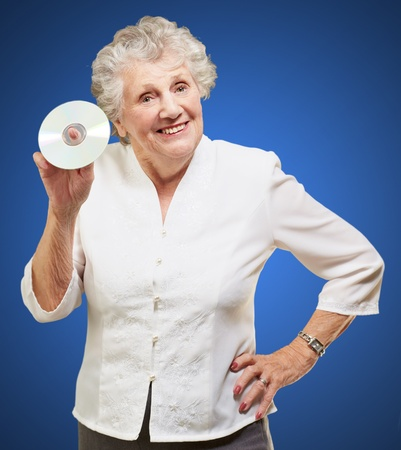 Senior woman holding cd isolated on blue background photo