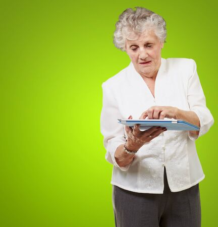 Senior woman using touchpad isolated on green background photo