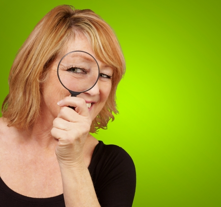 Woman using a magnifying glass isolated on green background photo