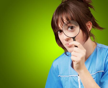 causation: Woman looking through magnifying glass isolated on green background Stock Photo