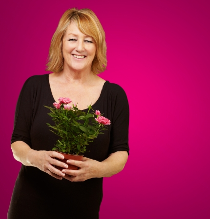 causation: Woman holding flower pot isolated on pink background