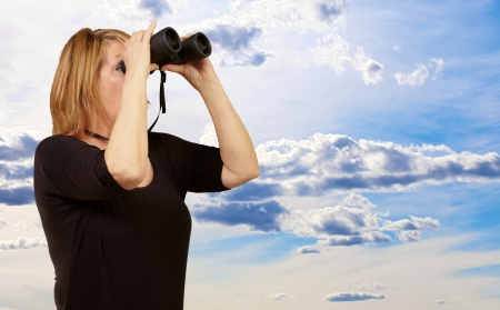 Women looking through binoculars, outdoor photo