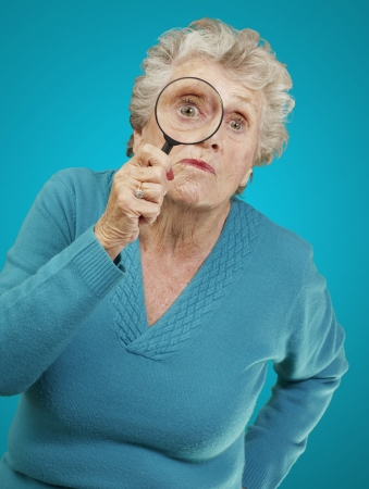 portrait of senior woman looking through a magnifying glass over blue background photo