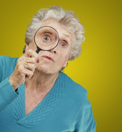 portrait of senior woman looking through a magnifying glass over yellow background photo