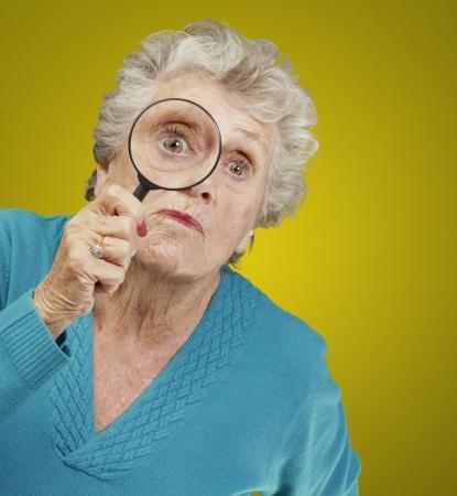 lupas: Retrato de la mujer mayor mirando a través de una lupa sobre fondo amarillo Foto de archivo