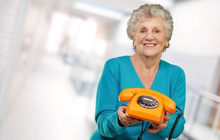 Mature Happy Woman Holding Telephone, Indoor Stock Photo - 16039389
