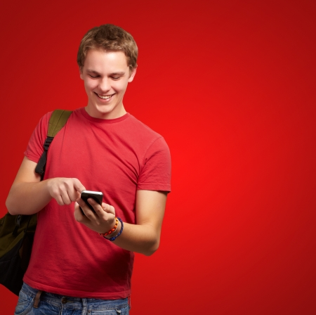 portrait of young man touching mobile screen over red background photo