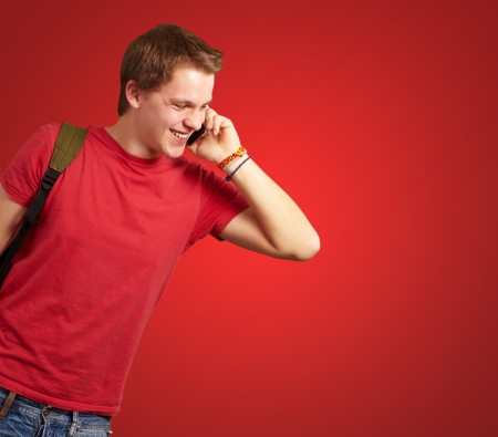 portrait of young man talking on mobile over red background photo