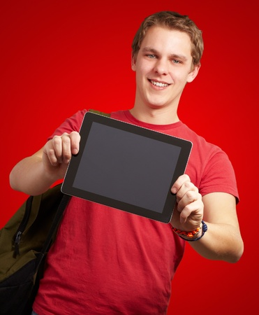 portrait of young man holding a digital tablet over red background photo