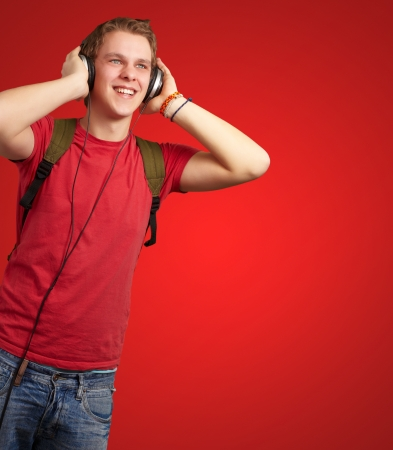 portrait of cheerful young student listening music with headphones over red photo