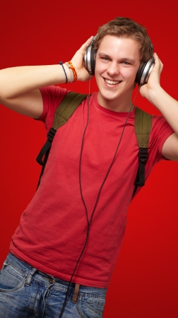 portrait of cheerful young student listening music with headphones over red Stock Photo - 16039104