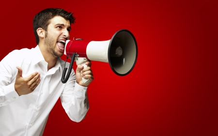 asking: portrait of young man shouting with megaphone over red background