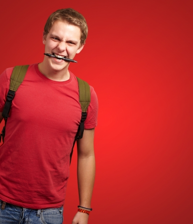 portrait of angry young man biting pen over red background photo