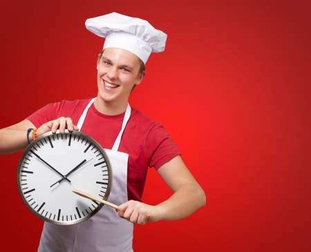 portrait of young cook man pointing a clock over red background photo