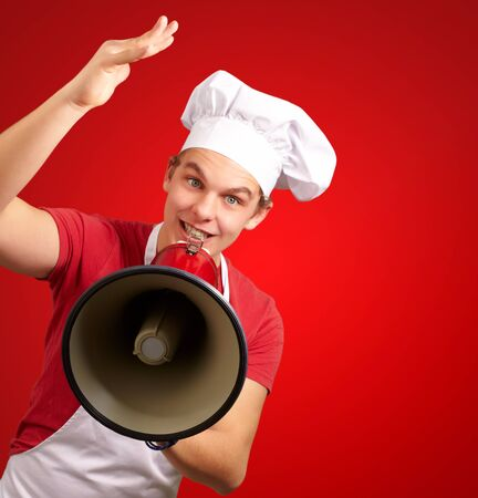 portrait of happy cook man shouting using megaphone over red background photo