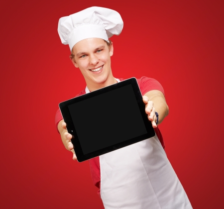 portrait of young cook man showing a digital tablet over red background