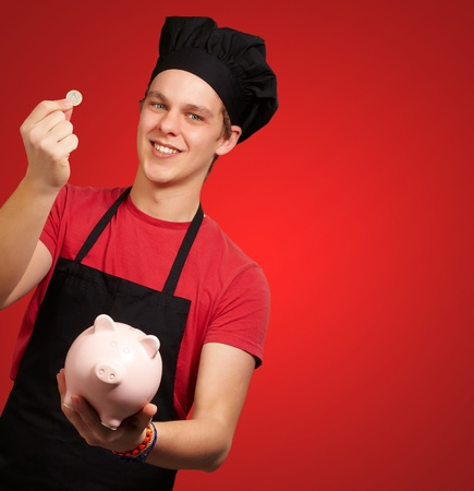 portrait of young cook man holding euro coin and piggy bank over red photo