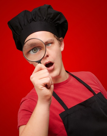 portrait of young cook man looking through a magnifying glass over red photo