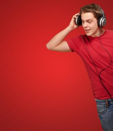 listening to music: Retrato de hombre joven escuchando m�sica en fondo rojo