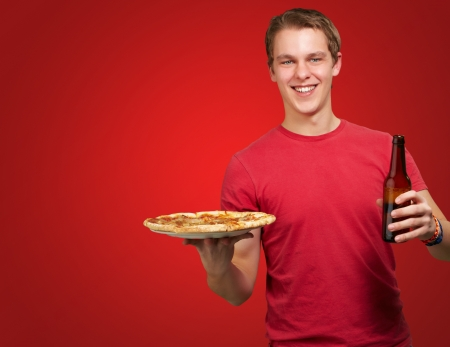 portrait of young man holding pizza and beer over red background photo