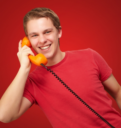 portrait of young man talking with vintage telephone over red background photo