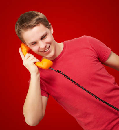portrait of young man talking on vintage telephone over red background photo