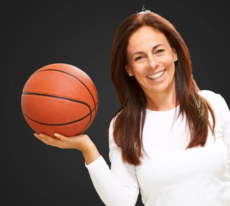 Woman Holding Basketball Isolated On black Background photo