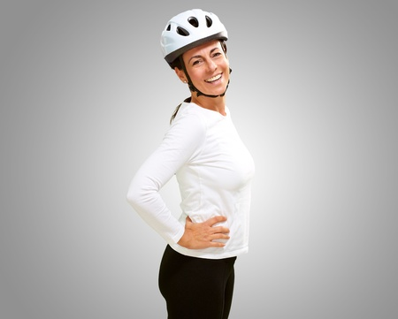 caucasion: woman wearing helmet against a grey background