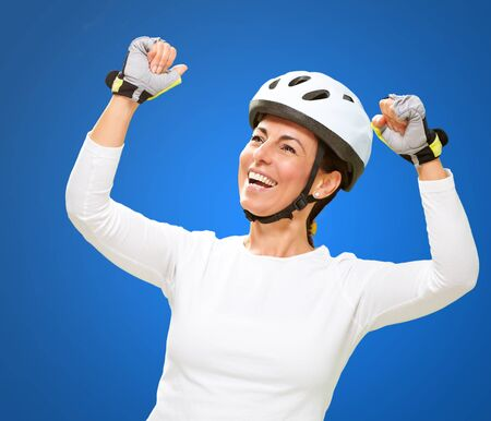 Woman Wearing Helmet Cheering Isolated On Blue Background photo