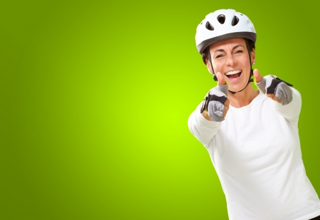 Woman Wearing Helmet Showing Both Thumbs Up Isolated On Green Background photo