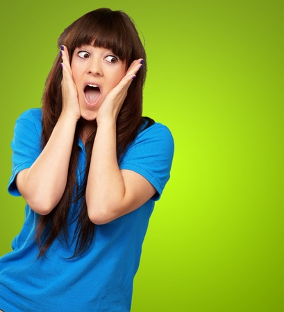portrait of surprised woman isolated on green background photo