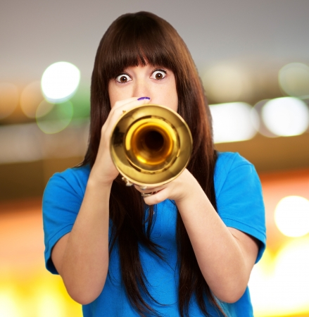 portrait of a teenager playing trumpet, outdoor photo