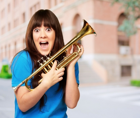 trumpeter: surprised woman holding trumpet, outdoor Stock Photo