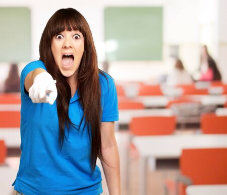 hands on hips: woman screaming and pointing finger, indoor Stock Photo