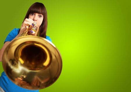 portrait of a young girl blowing trumpet on green background Stock Photo