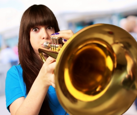 trumpeter: portrait of a young girl blowing trumpet, outdoor