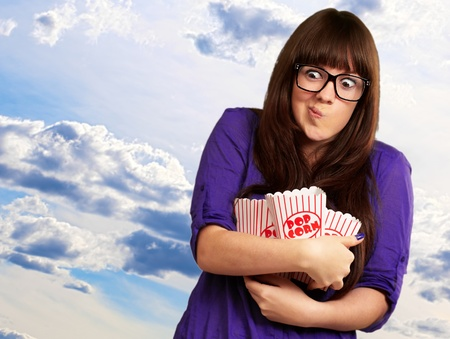 Portrait Of Young Woman Holding Popcorn Container, Outdoor photo