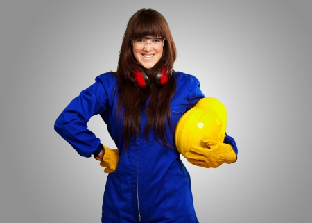 handglove: Portrait Of A Young Female Worker On Gray Background