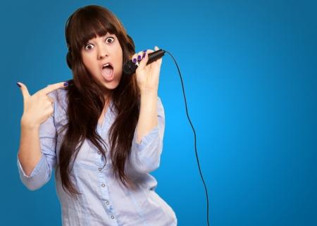 3a63f3c022d #16039231 - Retrato de una mujer joven con un micrófono sobre fondo azul