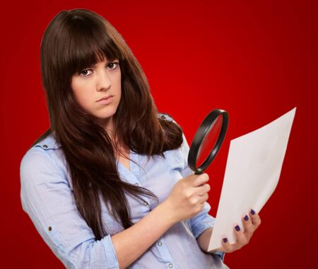 spy girl: Portrait Of A Girl Holding A Magnifying Glass And Paper On Red Background