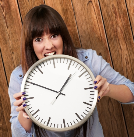 A Young Girl Holding A Clock And Angry, Indoor photo