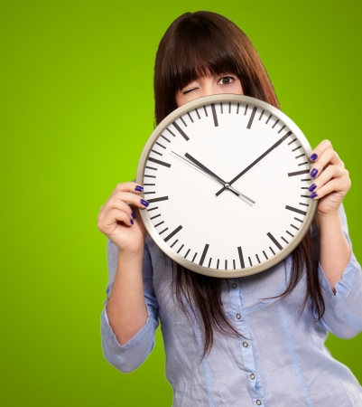 Woman Holding Clock Winking Isolated On Green Background photo