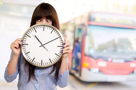 myopic: Woman Holding Clock With Squinted Eyes, Outdoor Stock Photo